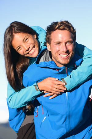 Happy couple piggyback in active lifestyle having fun on hike photo