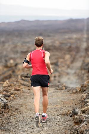 Trail runner man running cross-country run training outside for marathon photo