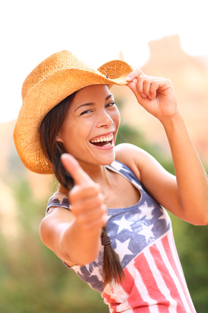 American cowgirl woman happy excited giving thumbs up wearing cowboy hat outdoors in countryside photo