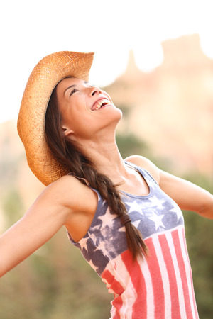 American cowgirl woman free and happy wearing cowboy hat outdoors in countryside photo