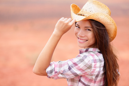 Cowgirl woman smiling happy on american prairie wearing cowboy hat photo