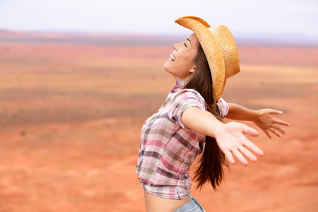 outstretched arms: woman happy and free on american prairie wearing cowboy hat with arms outstretched Stock Photo
