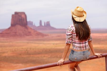 vaqueras: Mujer Vaquera vista de Monument Valley disfruta con el sombrero de vaquero. Joven y bella mujer en la mirada que se sienta al aire libre, Arizona Utah, EE.UU.. Foto de archivo