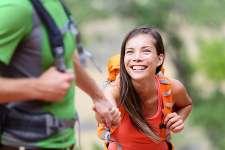challenges: Helping hand - hiking woman getting help on hike smiling happy overcoming obstacle. Active lifestyle hiker couple traveling. Beautiful smiling mixed race Asian Caucasian female model.