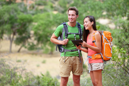 guide book: couple hiking using internet and tablet computer pc guide book app on hike in Zion National Park