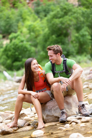 Young woman and man hiker sitting by river water creek enjoying view smiling photo