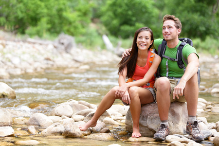 Hiking couple - hikers resting in Zion National Park. Young woman and man hiker sitting by river water creek enjoying view smiling happy. Young couple trekking, relaxing after hike, Utah, USA. photo
