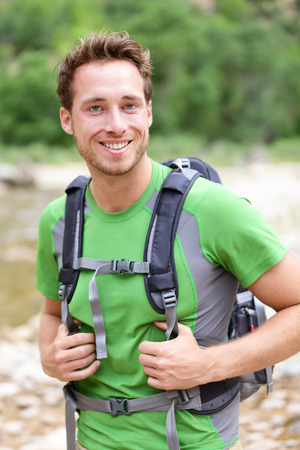 outdoorsman: Active man portrait of sporty guy hiking outdoors. Young male hiker smiling happy at camera wearing backpack outdoors during hike in forest nature. Caucasian male model outside.