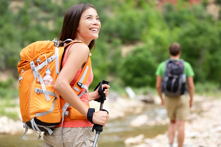 trekking pole: People hiking - woman hiker walking in Zion National Park, man in background. Hikers trekking by river water creek in forest enjoying view smiling happy. Young couple on trek hike in Utah, USA. Stock Photo