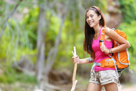 Asian woman hiker hiking in forest standing with backpack and wooden hike stick smiling photo
