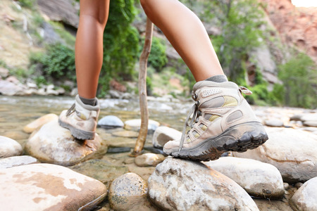 Hiking shoes on hiker outdoors walking crossing river creek