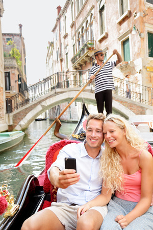 Romantic young beautiful couple taking self-portrait sailing in venetian canal in gondola. Italy. photo