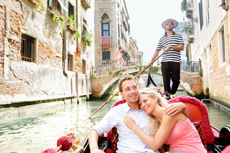 Romantic young beautiful couple sailing in venetian canal in gondola, Italy