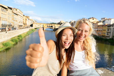 Cheerful girlfriends thumbs up smiling happy portrait outdoor by Ponte Vecchio during vacation holidays in Florence, Tuscany, Italy photo