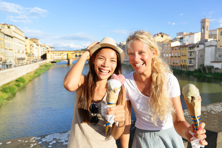 backpackers: Happy women friends eating ice cream on travel in Florence