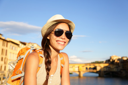 Backpacking women traveler on travel in Florence wearing sunglasses smiling