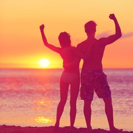 siluetas de enamorados: Ganar el concepto de éxito - feliz pareja playa al atardecer con los brazos levantó vítores extendido y feliz. Hermosa joven pareja de aptitud, hombre y mujer. Foto de archivo