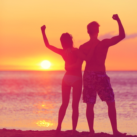 stretched: Winning success concept - happy beach couple at sunset with arms raised up outstretched cheering and happy. Beautiful young fitness couple, man and woman.