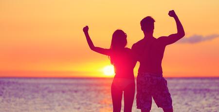 Gelukkig fitness mensen op het strand bij zonsondergang buigen tonen van spieren. Juichende winnende paar uitdrukking vreugde en succes bij elkaar omarmen. Man en vrouw op tropisch strand.