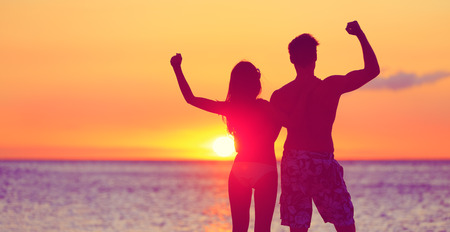 Happy fitness people on beach at sunset flexing showing muscles. Cheering winning couple expression joy and success together embracing. Man and woman on tropical beach. photo