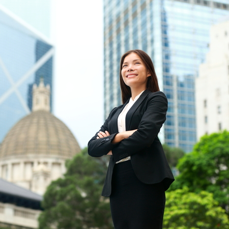 Businesswoman confident outside. Business woman standing proud and successful in suit cross-armed. Young multiracial Chinese Asian  Caucasian female professional in central Hong Kong.