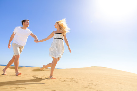 Couple holding hands running having fun under sun in playful and romantic relationship under sun and blue sky in desert. Two young lovers cheerful together on romance in summer. Joyful man and woman. photo