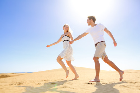 Relationship - happy couple playful romantic having fun under sun and blue sky in desert. Two young lovers running cheerful together on romance in summer. Cheerful Caucasian man and woman. photo