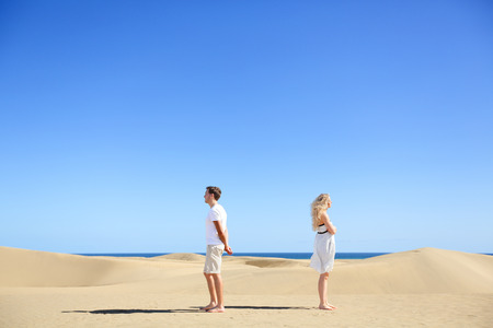 Relationship problem - upset couple argument. Angry couple in disagreement divorce and separation concept. Young couple with marriage problems. Woman and man conceptual image in desert under blue sky. Stock Photo