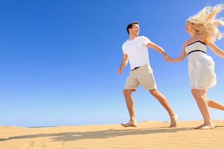 hot love: Happy couple in playful and romantic relationship having fun under sun and blue sky in desert. Two young lovers running cheerful together on romance in summer. Happy Caucasian man and woman. Stock Photo