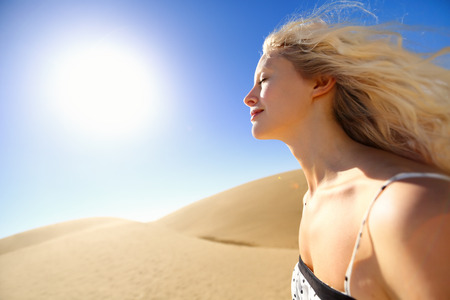 damages: Sun skin care woman enjoying desert sunshine outdoors. Blonde female model relaxing under hot heat getting tan smiling happy and relaxed.