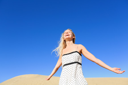 Happy woman enjoying sun and freedom under hot sun and blue sky in desert. Smiling young blonde female model free outside. photo