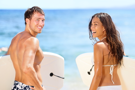 hawaii: Surfers on beach having fun in summer. Surfer woman and man with boogieboard smiling happy on beach on Hawaii. Multiracial couple Asian woman and Caucasian man in outdoor water activity during travel.