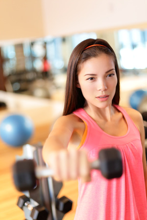 Fitness gym woman strength training lifting dumbbell weights in shoulder exercise. Female fitness girl exercising indoor in fitness center. Beautiful fit mixed race Asian Caucasian model training. photo