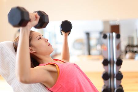 Gym vrouw krachttraining hijs halter gewichten in de schouder pers oefening. Vrouwelijke fitness meisje uitoefenen indoor in het fitnesscentrum. Mooie fit gemengd ras Aziatische Kaukasische model training. Stockfoto