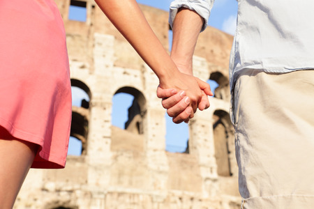 Colosseum, Rome, Italy - romantic couple holding hands on travel. Happy lovers on honeymoon in front of Coliseum. Love and travel concept.