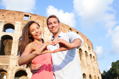 Romantic travel couple in Rome by Colosseum, Italy. Happy lovers on honeymoon showing heart sharped hands having fun in front of Coliseum. Love and travel concept with multiracial couple.