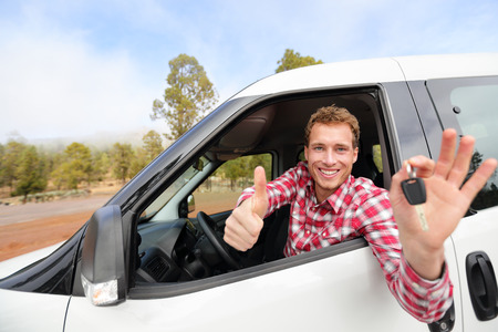 licence: Car driver showing car keys and thumbs up happy. Young man holding car keys for new car. Rental cars or drivers licence concept with male driving in beautiful nature on road trip. Stock Photo
