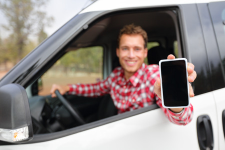 Smart phone man in car driving showing smartphone display smiling happy. Male driver using apps showing blank empty screen sitting in drivers seat. Focus on mobile cell phone. photo
