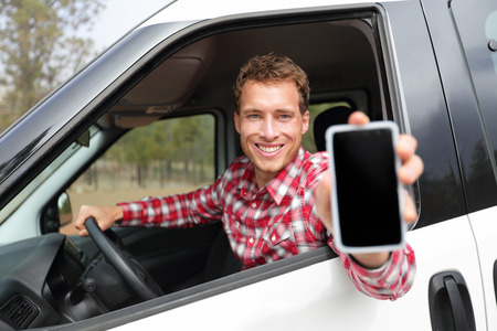Smartphone man in car driving showing smart phone display smiling happy. Male driver using app showing blank empty screen sitting in drivers seat. Focus on model. photo