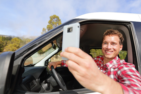 Driver taking photo with camera smartphone driving in car. Happy man taking picture with smart phone camera out window of car during travel road trip. Young Caucasian male model in his 20s. photo