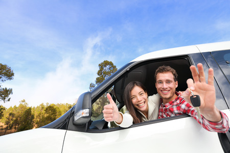New car - happy couple showing car keys driving having fun on road trip drive in rental car. Happy lifestyle with beautiful young interracial couple outdoors on travel. Man driver and woman passenger. photo