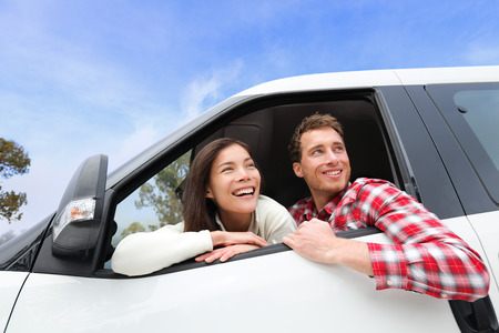 Couple lifestyle in new car looking out window. Driving young man and woman enjoying view on travel road trip in new car. Beautiful young multiracial young couple. Asian woman, Caucasian man. photo