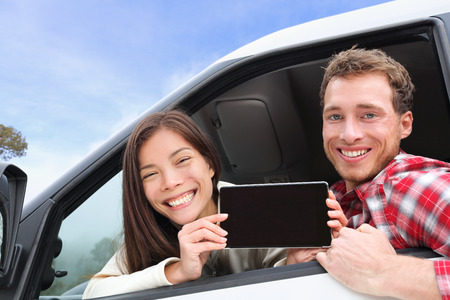 drivers: Tablet computer - couple driving in car showing screen with app or message. Young happy drivers on road trip. Asian woman, Caucasian man.