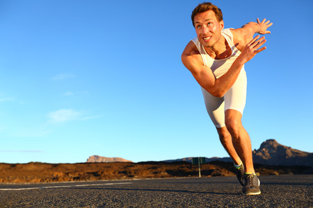 sprinting: Sprinting man running. Runner sprinter at fast speed training towards goals and success. Fit muscular male athlete in workout outdoors on road. Stock Photo
