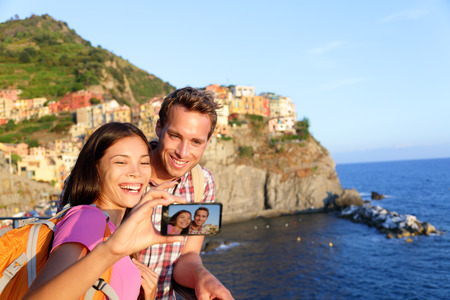 cinque: Selfie - couple taking picture in Cinque Terre, Italy with smartphone. Couple taking self portrait photo on holidays travel. Young man and woman backpacking in Manarola, Cinque Terre, Liguria, Italy