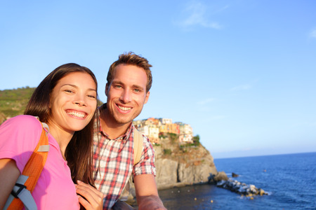 Selfie - couple in love in Cinque Terre, Italy. Romantic couple taking self portrait photo on holidays travel. Young man and woman backpackers on vacation in Manarola, Cinque Terre, Liguria, Italy photo