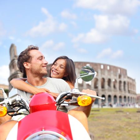 Rome couple on scooter by Colosseum, Italy  Romantic happy lovers driving scooter on honeymoon having fun in front of Coliseum  Love and travel concept with multiracial couple  photo
