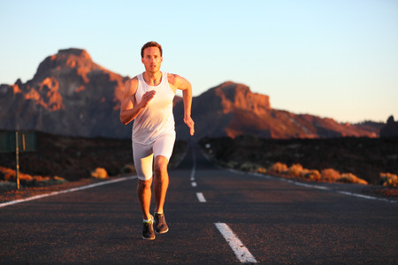 Athlete running sprinting at sunset on road  Male runner training in mountain landscape at night  Fit young muscular fitness sport model in his 20s  photo