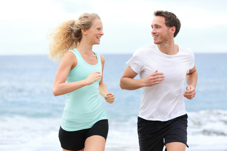 Running couple jogging exercising on beach talking and training as part of healthy lifestyle  Two fit runners jogging happy and smiling during workout  photo