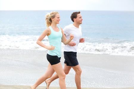 man working out: Running couple  Runners jogging on beach training together  Man and woman joggers exercising outdoors